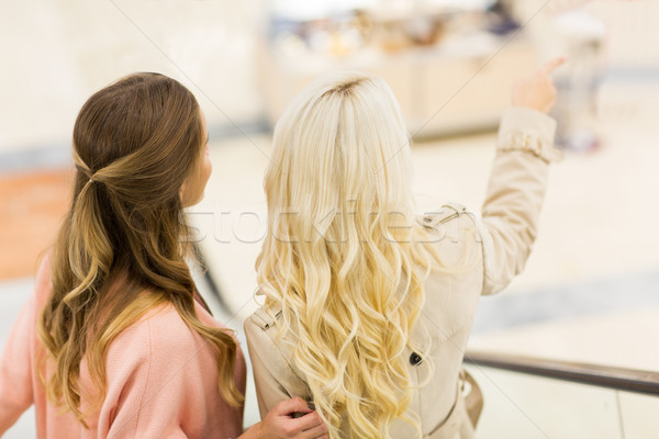young women in mall pointing finger to something Stock photo © dolgachov
