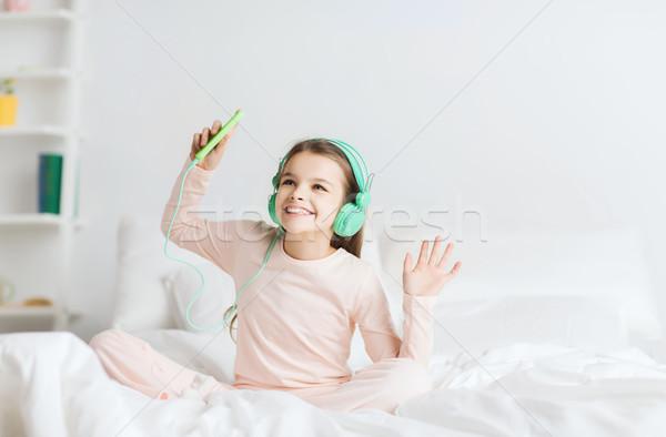 Menina sessão cama fones de ouvido pessoas Foto stock © dolgachov