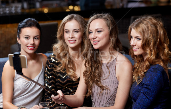 women with smartphone selfie stick at night club Stock photo © dolgachov