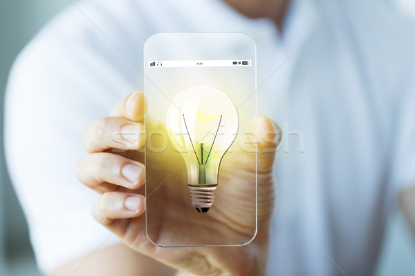 Stock photo: close up of hand with light bulb on smartphone