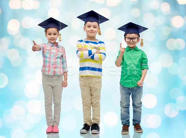 happy children in bachelor hats and eyeglasses Stock photo © dolgachov