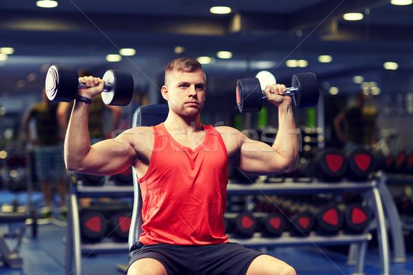 Jeune homme haltères muscles gymnase sport fitness Photo stock © dolgachov