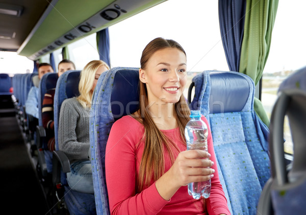 happy young woman with water bottle in travel bus Stock photo © dolgachov