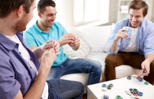 close up of male friends playing cards at home Stock photo © dolgachov