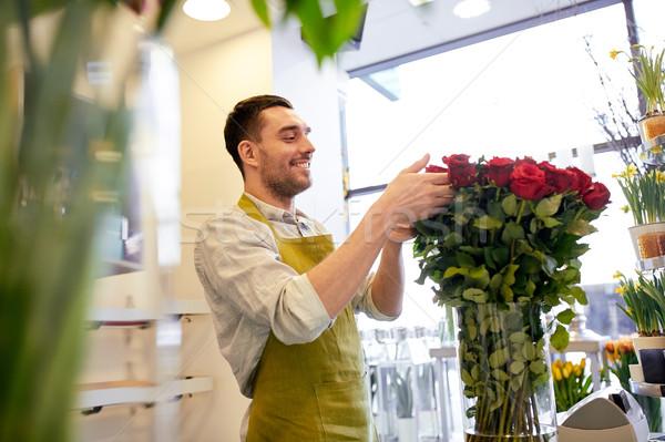 Souriant fleuriste homme roses personnes Photo stock © dolgachov