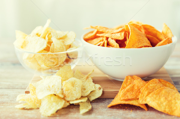 close up of potato crisps and nachos in glass bowl Stock photo © dolgachov