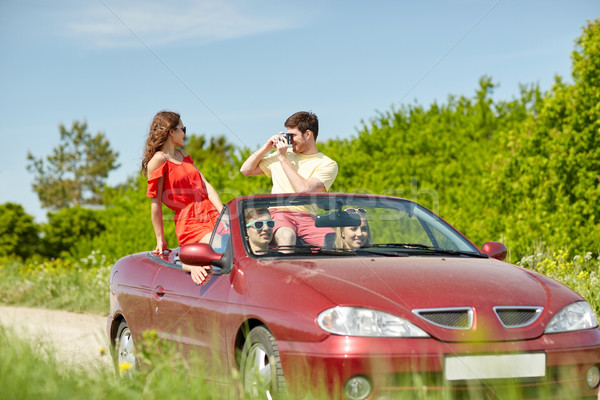 happy friends with camera driving in cabriolet car Stock photo © dolgachov