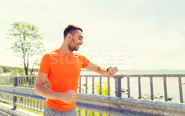 Stock photo: smiling young man with smart wristwatch at seaside