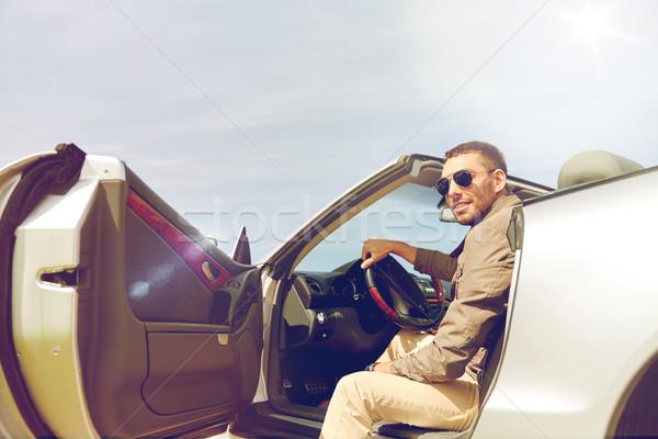 Felice uomo apertura porta cabriolet auto Foto d'archivio © dolgachov