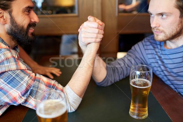 happy male friends arm wrestling at bar or pub Stock photo © dolgachov