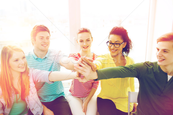 smiling students making high five gesture sitting Stock photo © dolgachov