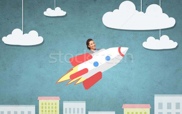 Zakenvrouw vliegen raket boven cartoon stad Stockfoto © dolgachov