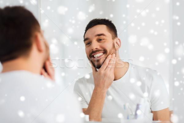 happy young man looking to mirror at home bathroom Stock photo © dolgachov