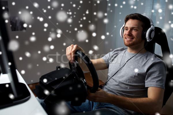 man playing car racing video game at home Stock photo © dolgachov