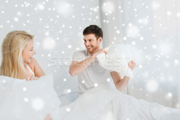 happy couple having pillow fight in bed at home Stock photo © dolgachov