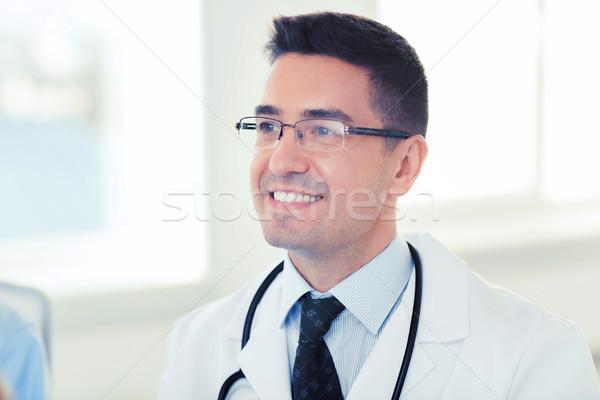 smiling male doctor in white coat and eyeglasses Stock photo © dolgachov