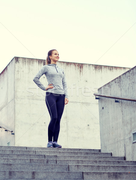 smiling sportive woman on stairs at city Stock photo © dolgachov