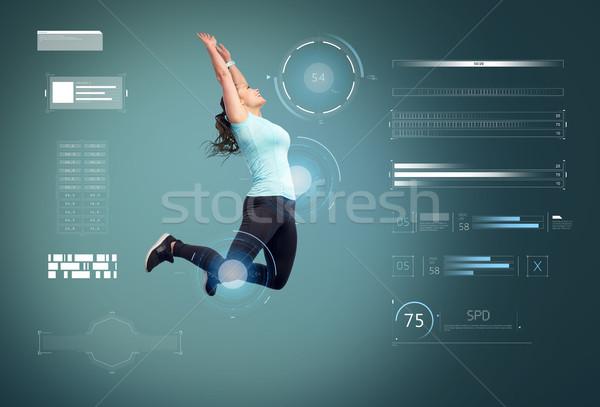 Heureux souriant jeune femme sautant air Photo stock © dolgachov