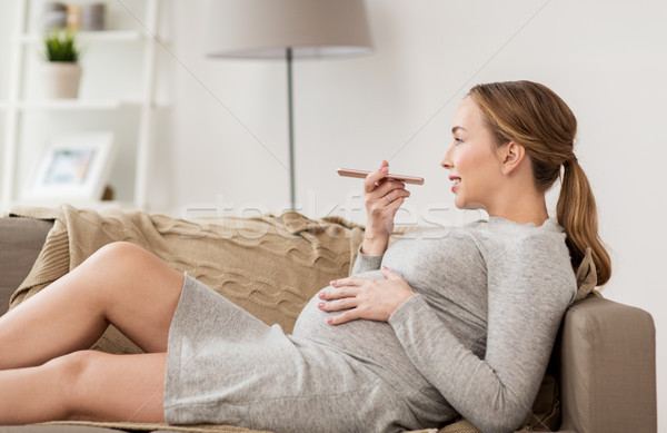 pregnant woman using voice recorder on smartphone Stock photo © dolgachov