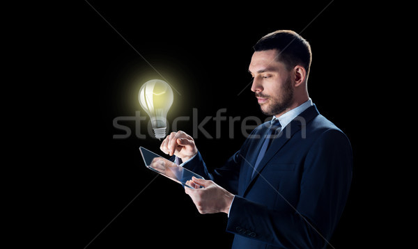 businessman with tablet pc and lightbulb Stock photo © dolgachov