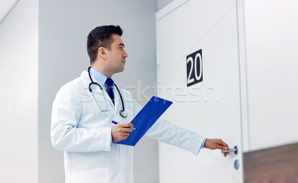 doctor with clipboard opening hospital ward door Stock photo © dolgachov
