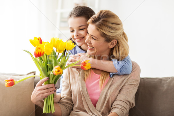 happy girl giving flowers to mother at home Stock photo © dolgachov