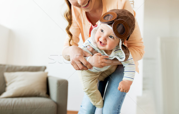 Stock photo: happy mother with baby wearing pilot hat at home
