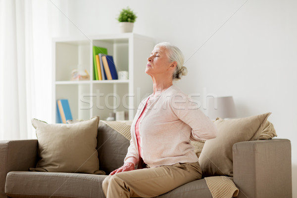 senior woman suffering from pain in back at home Stock photo © dolgachov