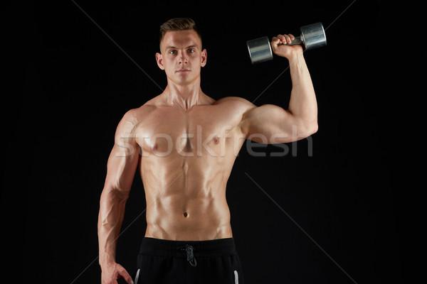 man with dumbbell exercising over black background Stock photo © dolgachov