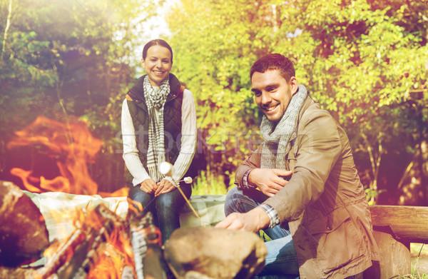 happy couple roasting marshmallow over camp fire Stock photo © dolgachov
