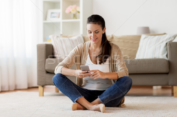 happy woman texting message on smartphone at home Stock photo © dolgachov