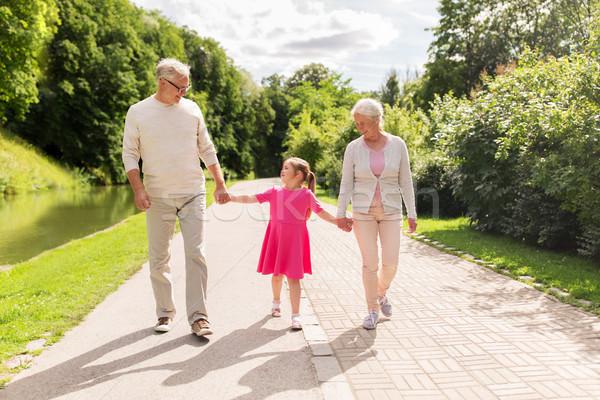 senior grandparents and granddaughter at park Stock photo © dolgachov