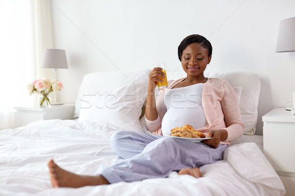 happy pregnant woman with croissant buns at home Stock photo © dolgachov