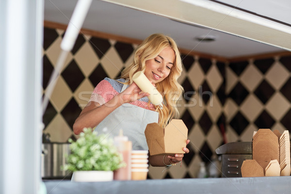 happy saleswoman making wok at food truck Stock photo © dolgachov