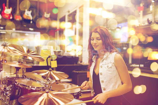 female musician playing drum kit at music store Stock photo © dolgachov