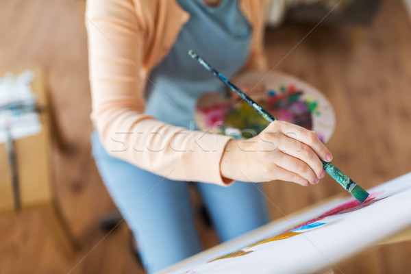 artist with palette and brush painting at studio Stock photo © dolgachov