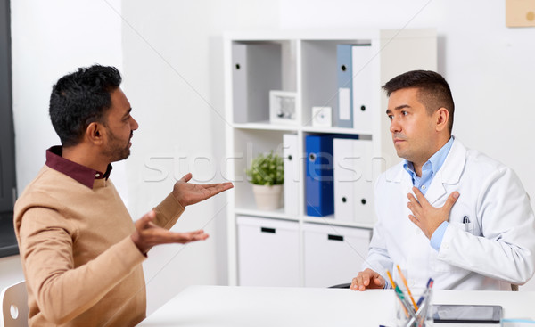 doctor and displeased male patient argue at clinic Stock photo © dolgachov