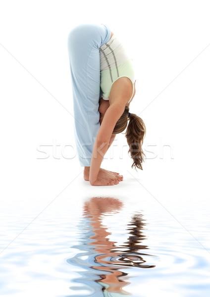uttanasana standing forward bend on white sand Stock photo © dolgachov