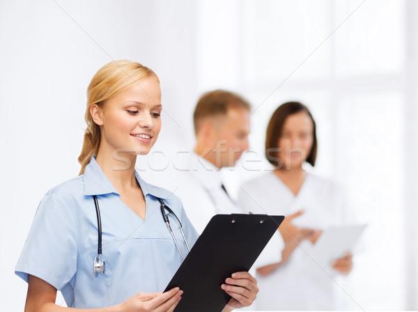 smiling female doctor or nurse with clipboard Stock photo © dolgachov
