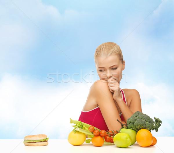 doubting woman with fruits and hamburger Stock photo © dolgachov