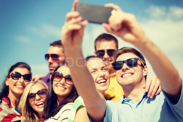 Stock photo: group of friends taking picture with smartphone