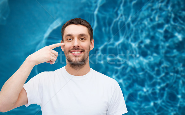 smiling young handsome man pointing to eyes Stock photo © dolgachov