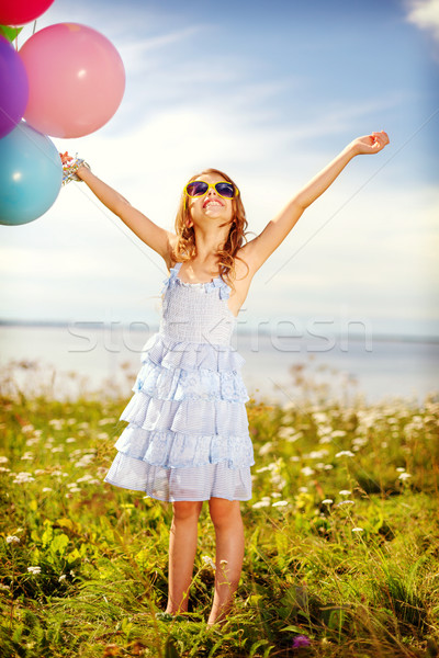 happy girl waving hands with colorful balloons Stock photo © dolgachov