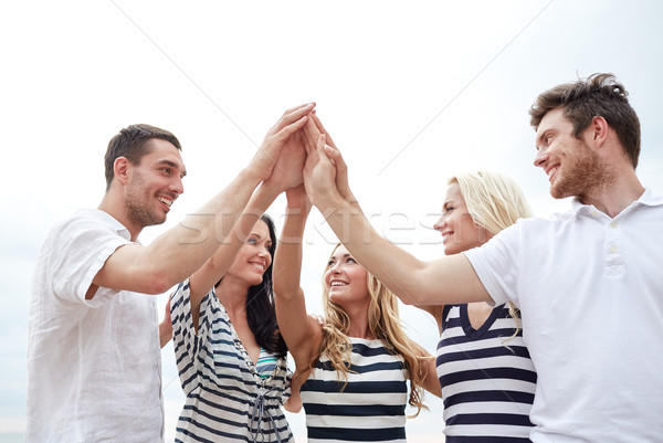 Stock photo: smiling friends making high five gesture outdoors
