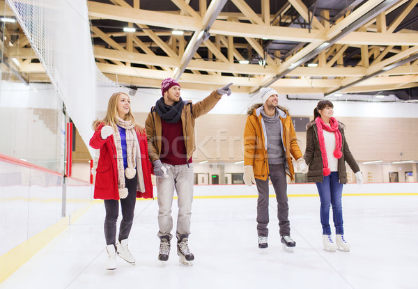 happy friends pointing finger on skating rink Stock photo © dolgachov