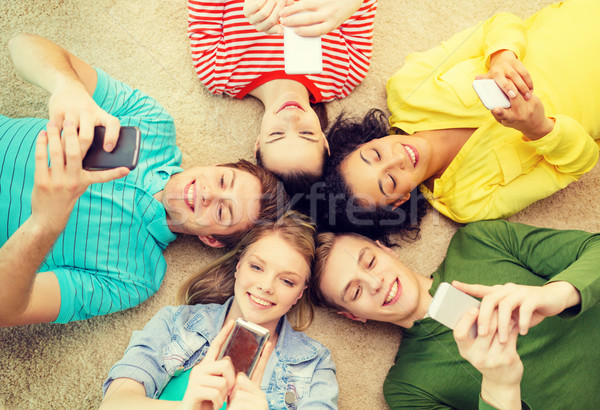 group of smiling people lying down on floor Stock photo © dolgachov