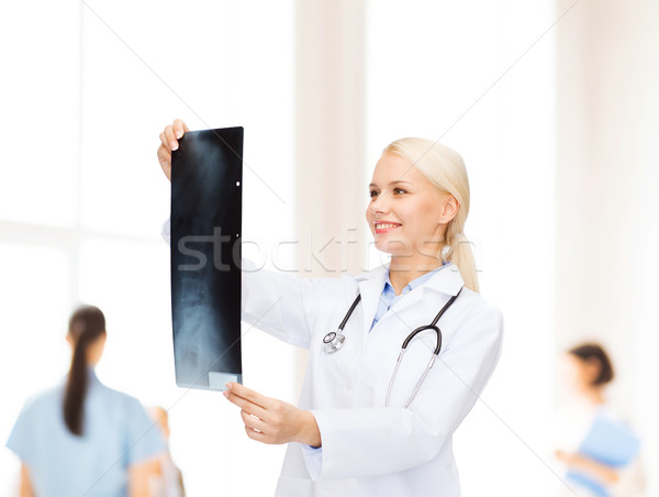 smiling female doctor looking at x-ray image Stock photo © dolgachov