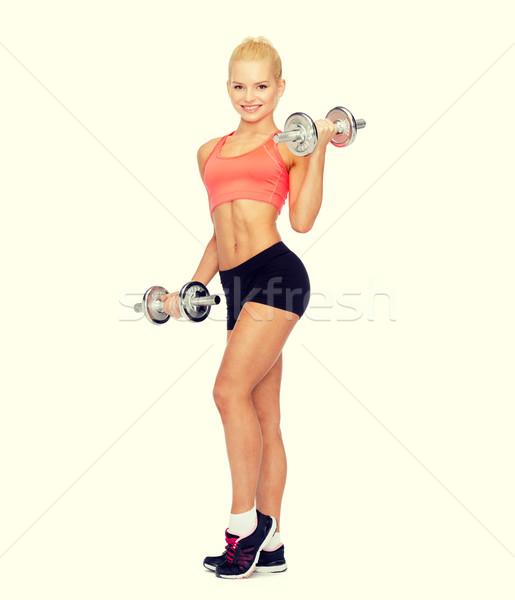Uśmiechnięty kobieta ciężki stali hantle Zdjęcia stock © dolgachov