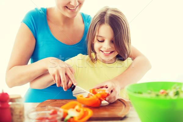 smiling little girl with mother chopping pepper Stock photo © dolgachov
