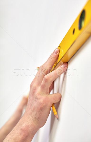 Homme mains niveau mur Photo stock © dolgachov